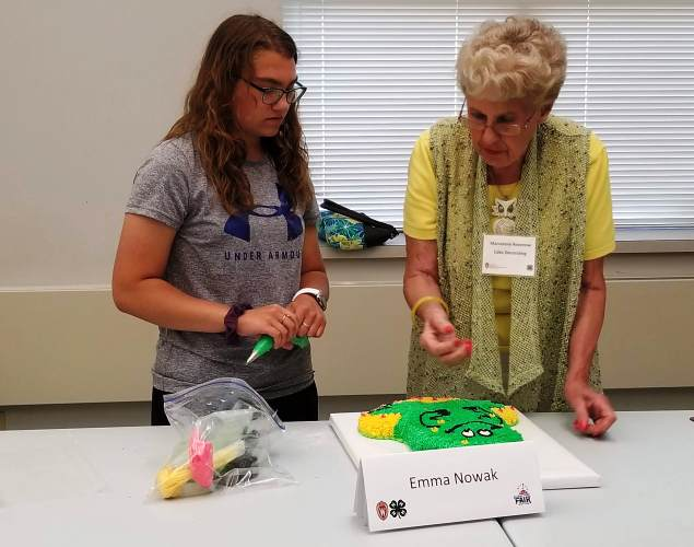 Emma N. of Naugart Knights explains how she created her Cake Decorating exhibit to the judge at the 2019 Cake Revue, a pre-fair event for the Wisconsin Valley Fair.